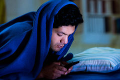 Les hommes sociaux d'intoxiqué de media sur le lit pas dorment parce que téléphone intelligent de jeu, couvrant sa tête de couver image libre de droits