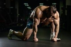 Les hommes sportifs de bodybuilder fort brutal pompant muscles avec d Photographie stock