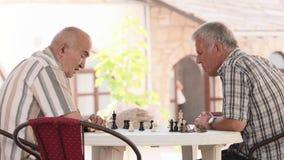 Les hommes supérieurs jouent aux échecs image stock