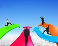 Les hommes sur quatre flèches de couleur vont en avant Photo libre de droits