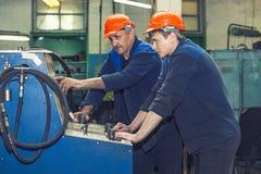 Les hommes travaillent à la vieille usine pour l'installation de l'équipement image stock