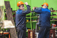 Les hommes travaillent à la vieille usine pour l'installation de l'équipement photo libre de droits
