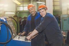 Les hommes travaillent à la vieille usine pour l'installation de l'équipement photographie stock libre de droits
