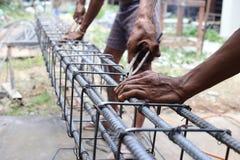 Les hommes travaillent aux étriers de faisceau Photographie stock libre de droits