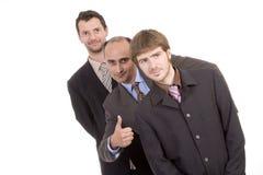 les hommes trois réussis d'affaires manient maladroitement vers le haut Image stock