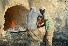 Les hommes utilisant les ?charpes principales traditionnelles et injecte le travail ? un four ext?rieur de production de charbon  photographie stock
