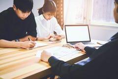 Les hommes utilisent un écran vide de l'ordinateur Sur la table dans le bureau où les femmes s'asseyent ensemble emploie l'idée d Images libres de droits