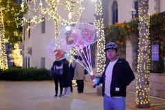 Les hommes vendent les ballons lumineux la nuit, image de srgb