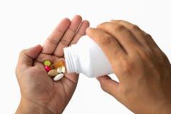Les hommes versent des pilules dans leurs mains Photos stock