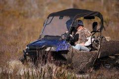 Les hommes vont off-roading dans un marais avec un ATV photo stock