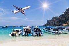 Les hors-bords ont amarré en mer tropicale avec l'atterrissage d'avion ci-dessus Image stock