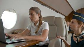 Les hostes d'air interrogent la femme d'affaires sûre au sujet du service à l'intérieur des avions de carlingue de jet privé banque de vidéos