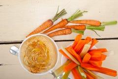 Les houmous frais plongent avec la carotte et le céleri crus Photos libres de droits