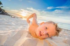 Les huit années belles de garçon sur la plage exécute des croquis acrobatiques Photo libre de droits