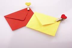 Les icônes en forme de coeur attachées à coloré enveloppe Images libres de droits