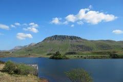 Les idris de Cadair derrière un lac de montagne se sont baignés en soleil en parc national de snowdonia Photographie stock libre de droits