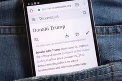 Les informations sur Donald Trump sur le site Web de Wikipedia montré sur le smartphone caché dans des jeans empochent photographie stock
