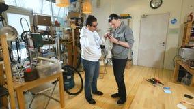 Les ingénieurs dans le laboratoire discutent le bras bionique robotique fait sur l'imprimante 3D banque de vidéos
