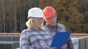 Les ingénieurs de femme et d'homme au chantier de construction ont l'amusement discutant le projet clips vidéos