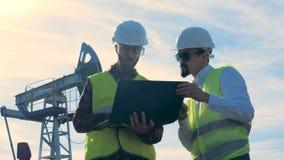 Les ingénieurs masculins travaillent avec un ordinateur portable sur un gisement de pétrole, fin  clips vidéos