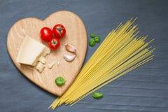 Les ingrédients de pâtes de spaghetti soustraient la nourriture sur le fond noir Images stock