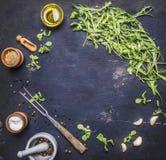Les ingrédients pour faire cuire la nourriture végétarienne, le pétrole d'arugula avec du sel et l'endroit de poivre pour le text Photographie stock libre de droits