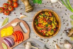 Les ingrédients pour l'oignon de nourriture poivrent l'ail et les ustensiles sur une table en bois vue supérieure des verts de lé Images stock