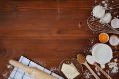Les ingrédients pour la pâte de cuisson comprenant la farine, oeufs, lait, le beurre, sucre, battent et goupille sur le fond rust Image stock