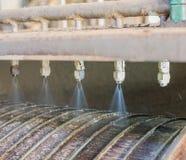 Les injecteurs pulvérisent l'eau sur le tambour souillé photos stock