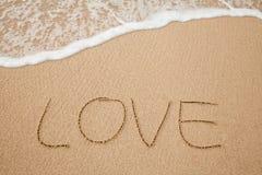 Les inscriptions de l'amour sur la plage de sable Image stock