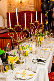 Les invités d'anniversaire ajournent l'arrangement avec les fleurs fraîches dans le noir et le style d'or, d'intérieur Photos stock
