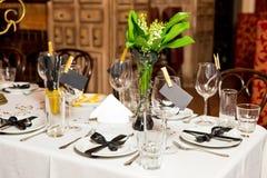 Les invités d'anniversaire ajournent l'arrangement avec les fleurs fraîches dans le noir et le style d'or, d'intérieur Photographie stock