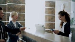Les invités d'homme d'affaires et de femme d'affaires viennent à la fille de réceptionniste et à la facture de paiement avec la c clips vidéos