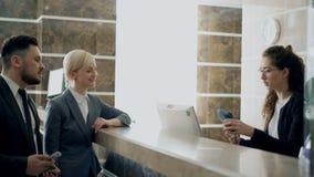 Les invités d'homme d'affaires et de femme d'affaires viennent chez le réceptionniste se tenant au bureau et à la facture de paie clips vidéos