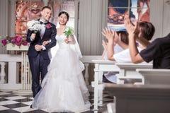 Les invités de mariage applaudissant pour des nouveaux mariés couplent tenir des fleurs dans l'église Photos stock
