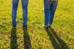 Les jambes élégantes de couples sur l'herbe ensoleillée dans le pré en été, voyagent ensemble le concept, l'espace pour le texte Photo libre de droits