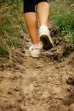 les jambes élégantes de femme dans des espadrilles marchant sur la terre, exercice se surpassent Photo stock
