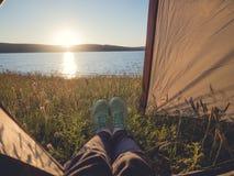 Les jambes équipent dans une tente de touristes sur le paysage marin pittoresque d'été Vue des pieds, tir de point de vue Image libre de droits