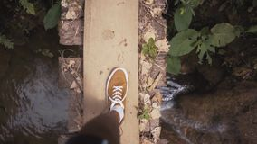 Les jambes équipent la marche sur un pont en bois, vue d'en haut clips vidéos