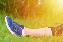Les jambes avec des espadrilles folâtre des filles sur une pelouse verte Le concept des loisirs et des sports, lumière du soleil Photo stock