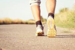 Les jambes courantes de l'homme sur la route pavée Photographie stock