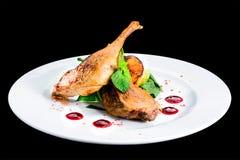 Les jambes cuites délicieuses juteuses de canard ont servi avec les herbes et la sauce dedans photo stock