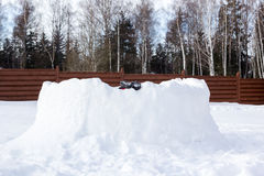 Les jambes d'enfant collent hors du mur de la forteresse de neige Image stock