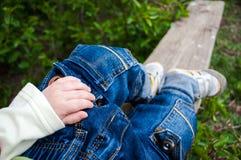 Les jambes d'un petit enfant sur un banc en bois Photographie stock