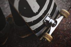 Les jambes d'un type dans des espadrilles avec une planche à roulettes sur la rue Plan rapproché de roue et de suspension de pati Photographie stock