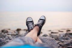 Les jambes d'un type dans des espadrilles sur la plage Photos stock
