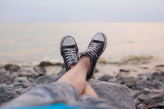 Les jambes d'un type dans des espadrilles sur la plage Images libres de droits
