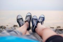 Les jambes d'un type et d'une fille le soir sur la plage Photographie stock