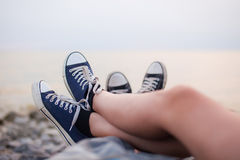 Les jambes d'un type et d'une fille le soir sur la plage Photos libres de droits