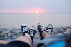 Les jambes d'un type et d'une fille le soir sur la plage Image stock
